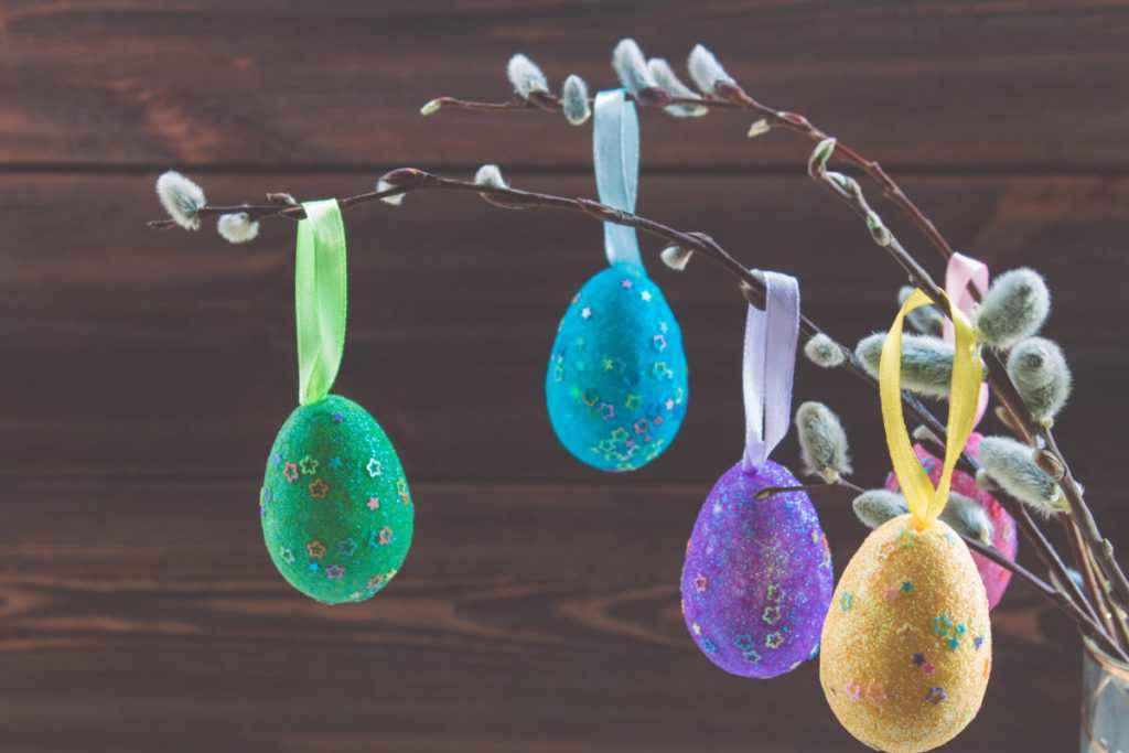 albero di pasqua con rami di salice e uova glitter colorate