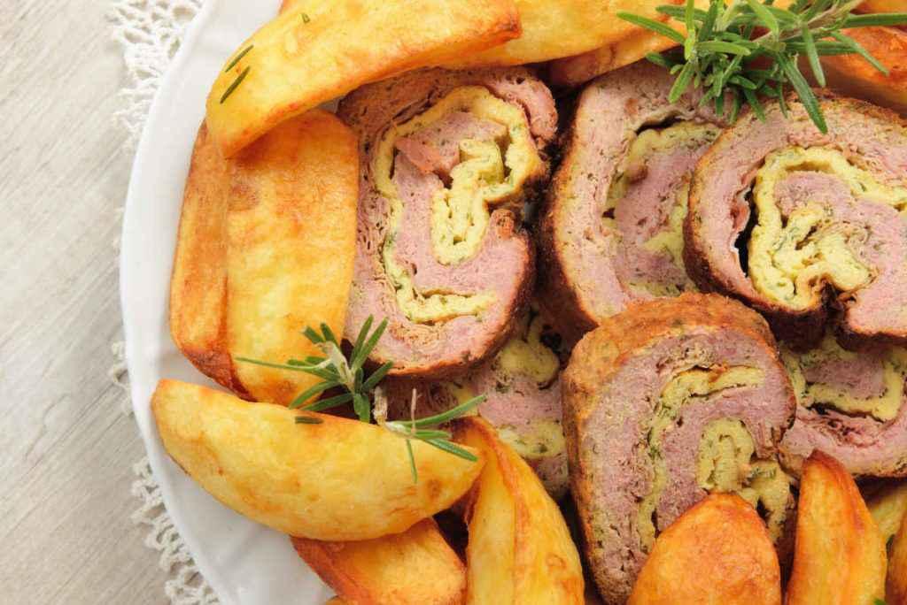fette di polpettone ripieno di prosciutto con contorno di patate arrosto