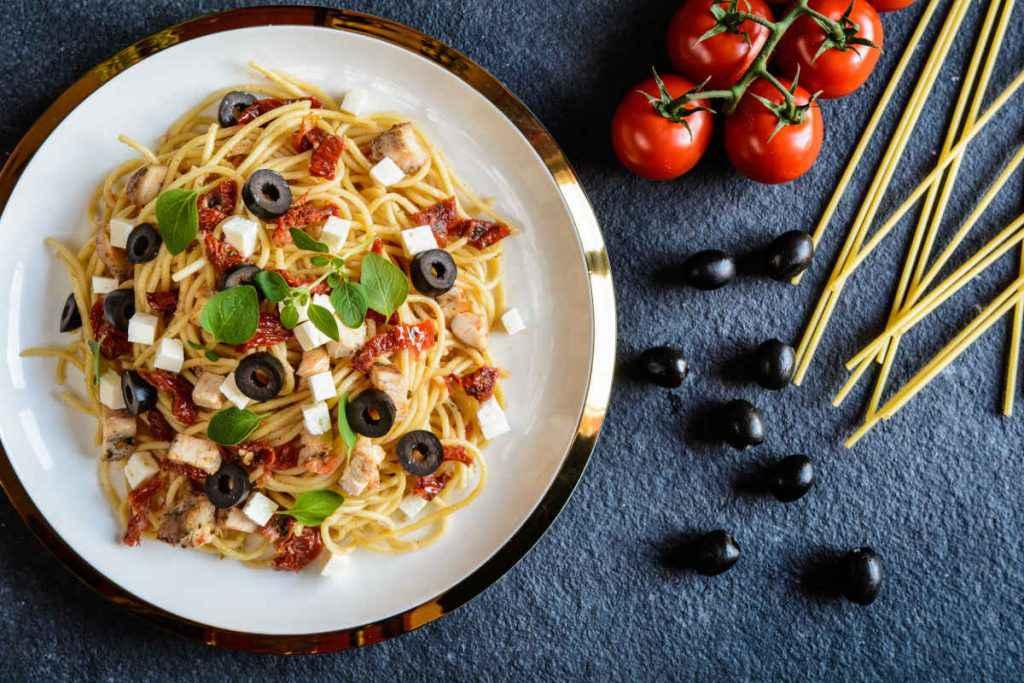 piatto di pasta con pomodori secchi olive e feta
