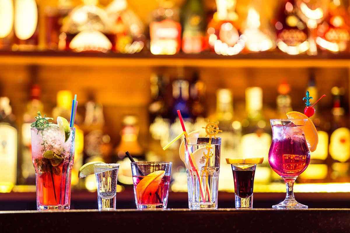 Bancone da bar con coktail alcolici colorati in bicchieri differenti