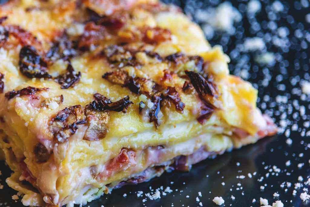 porzione di lasagne al radicchio con speck e besciamella