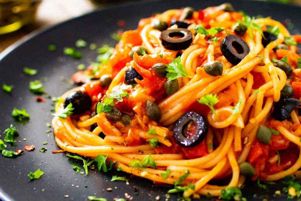 piatto di pasta con spaghetti alla puttanesca per il pranzo di ferragosto