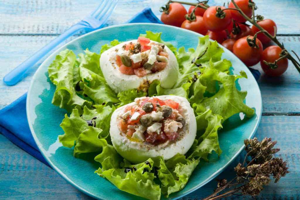 piatto con mozzarella ripiena di verdure su letto di insalata per antipasti senza cottura