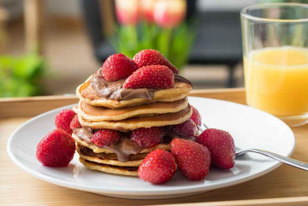 pancake alla nutella e fragole su piatto bianco