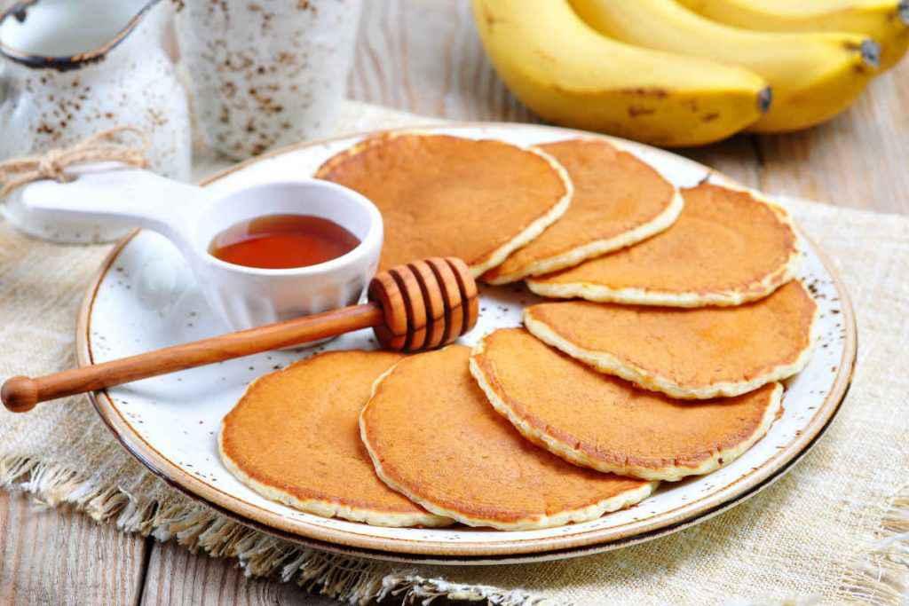 Piatto pieno di pancake senza uova con sciroppo di acero e banane