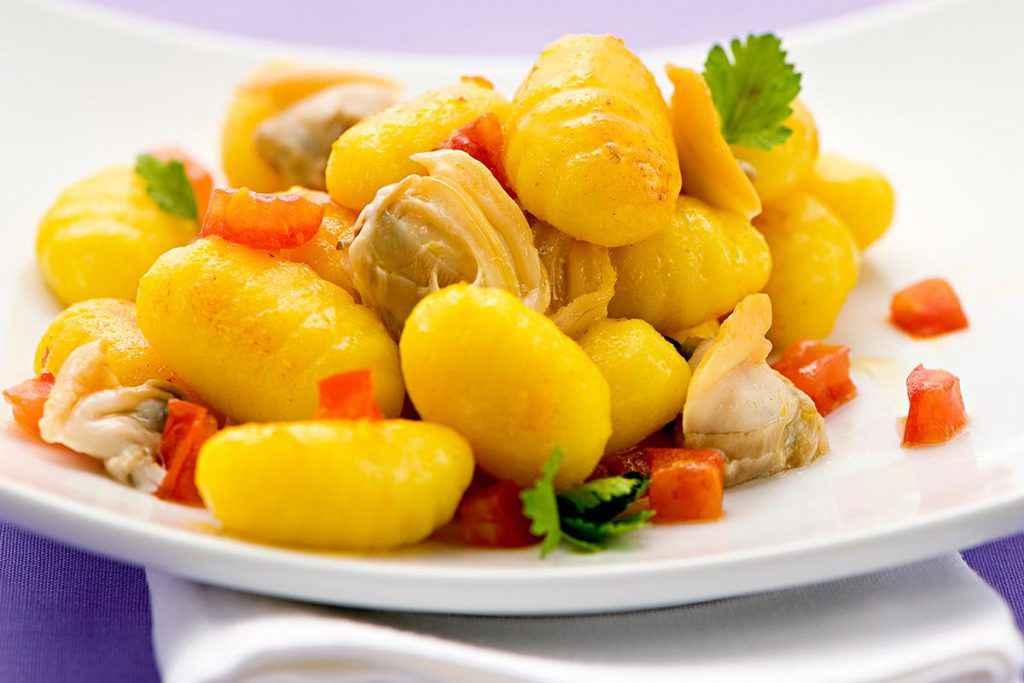Piatto di gnocchi con vongole e pomodorini freschi