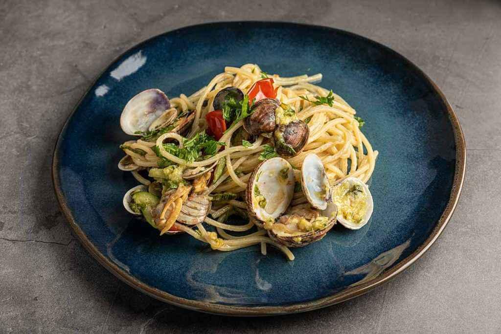 Piatto di spaghetti con le vongole e le zucchine