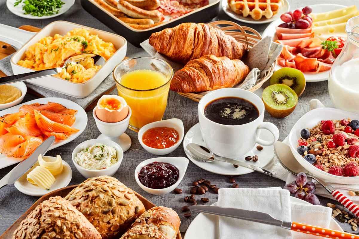 cosa mangiare a colazione salato o dolce, cosa mangio a colazione mangiare sano con colazione dolce salata, tavola imbandita con cibi per colazione e bevande