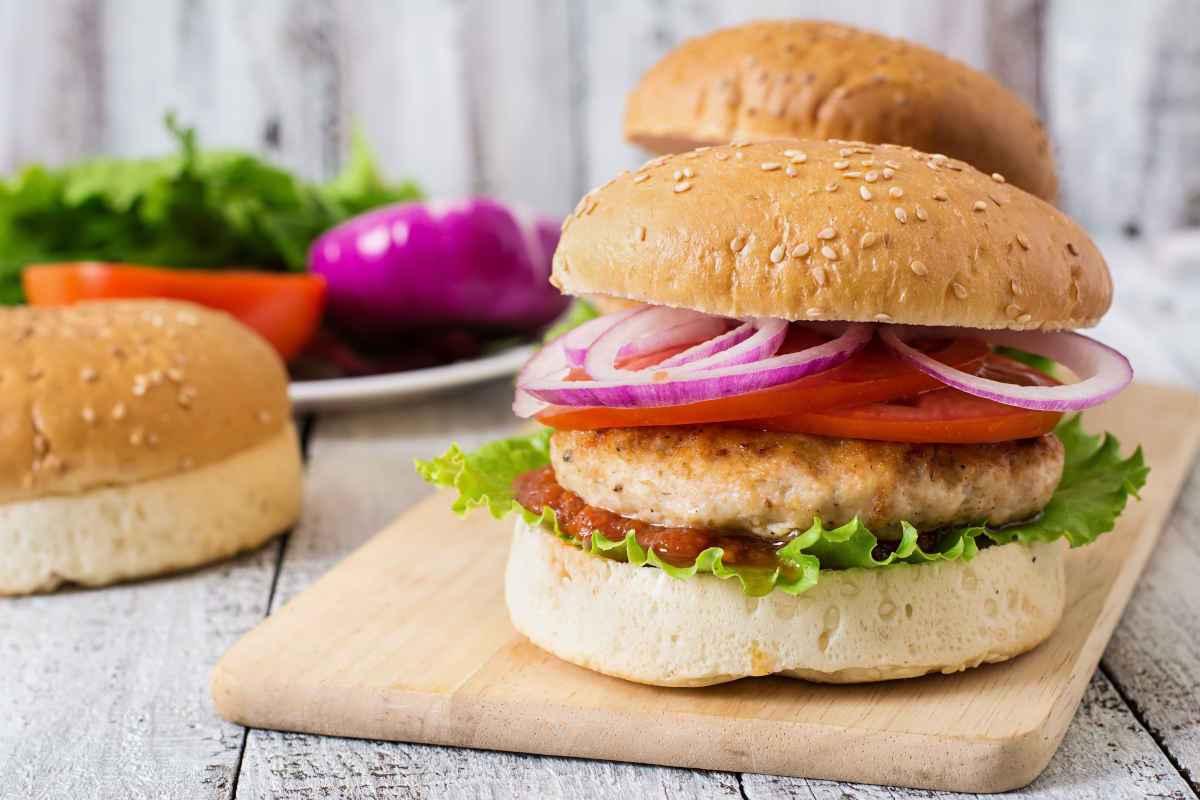 hamburger di pollo nel panino con pomodoro e cipolla