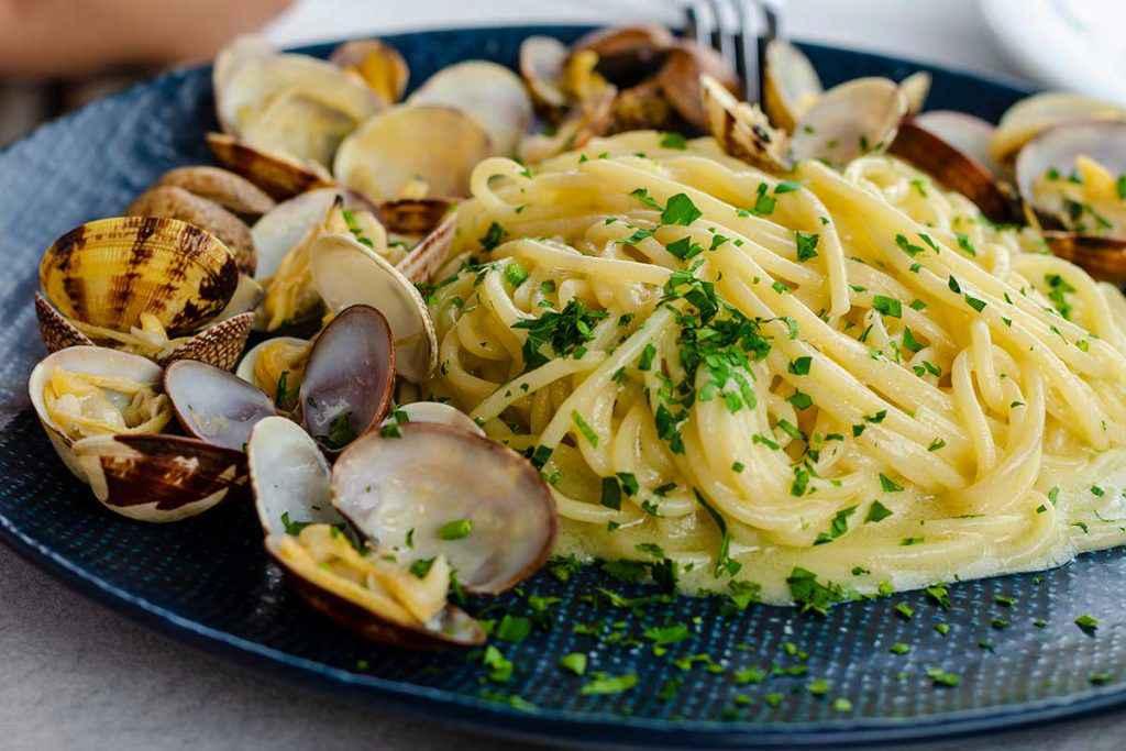 Piatto di spaghetti con vongole fresche e prezzemolo tritato