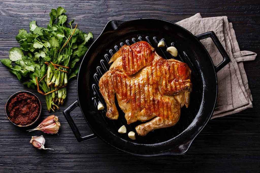 Pollo intero cotto sulla piastra di ghisa