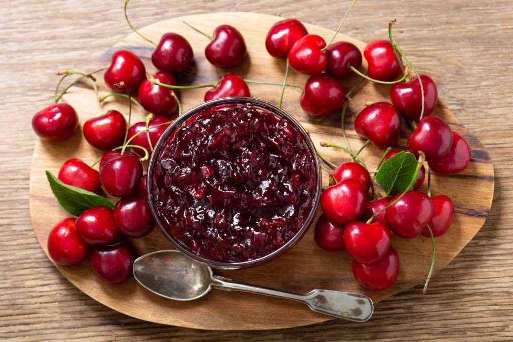 confettura di ciliegie e frutta fresca su tagliere di legno