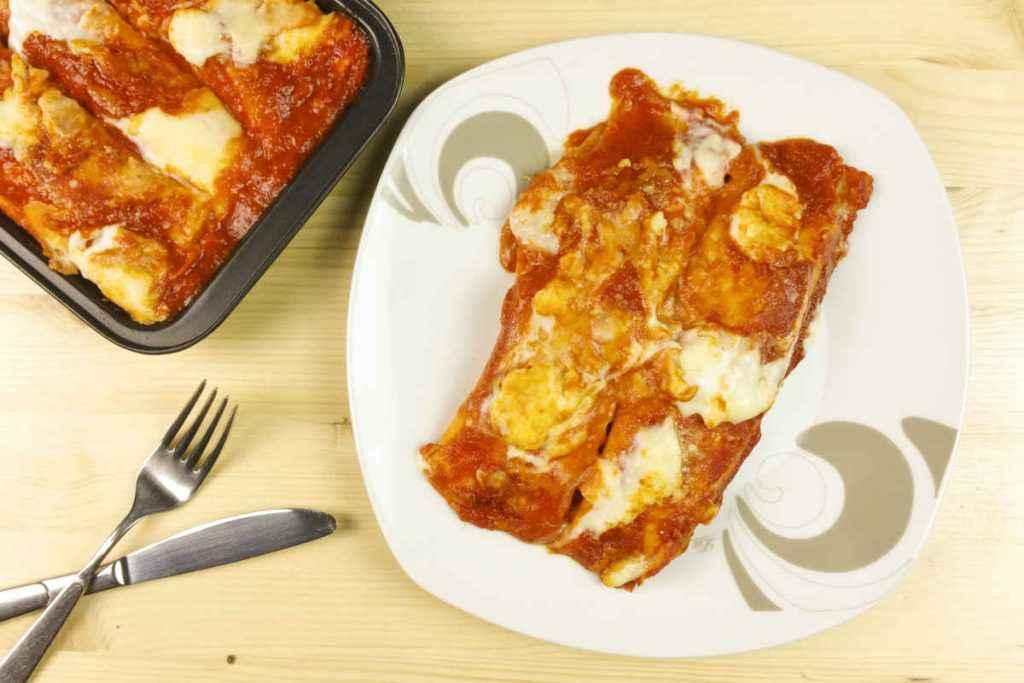 piatto con crepes ripiene di mozzarella e coperte di pomodoro