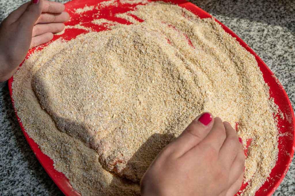 donna mentre prepara le cotolette panate