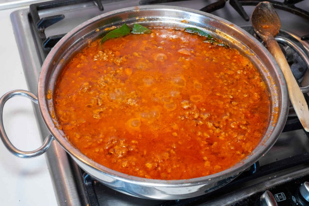 pentola sul fuoco con ragù bolognese in cottura