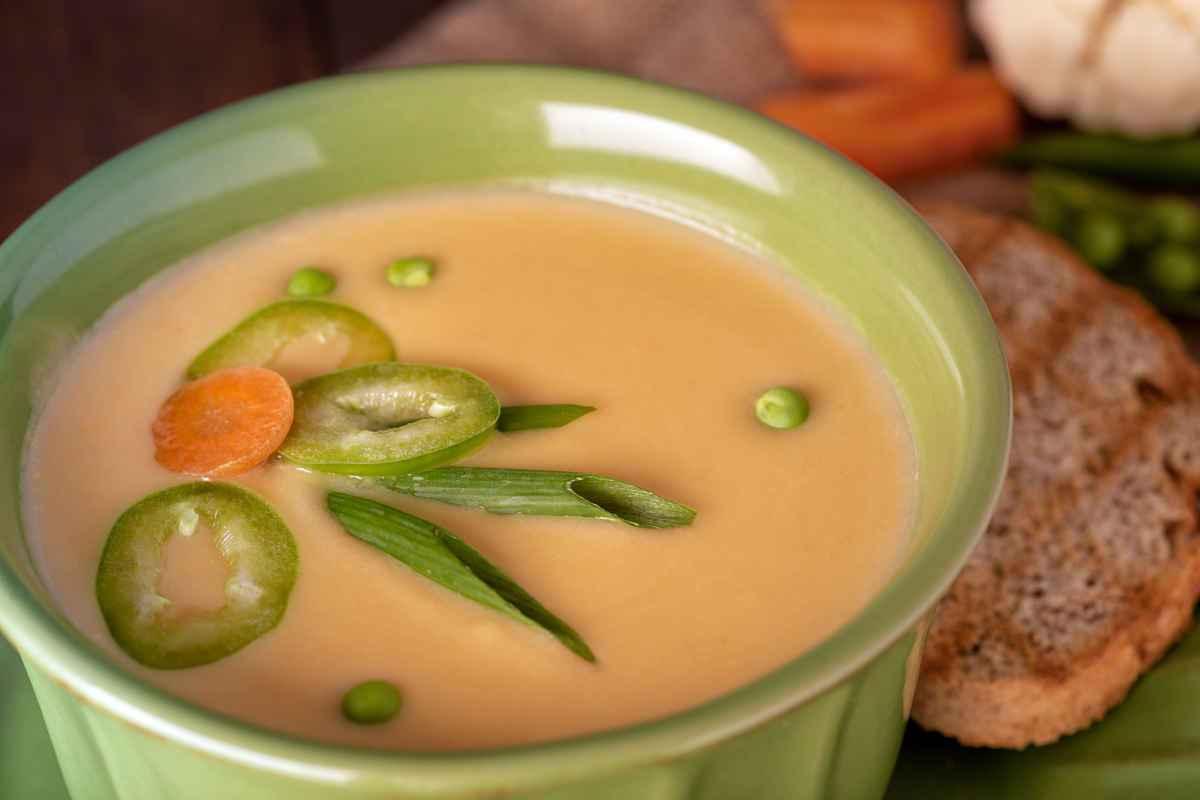 scodella con zuppa di piselli e carote