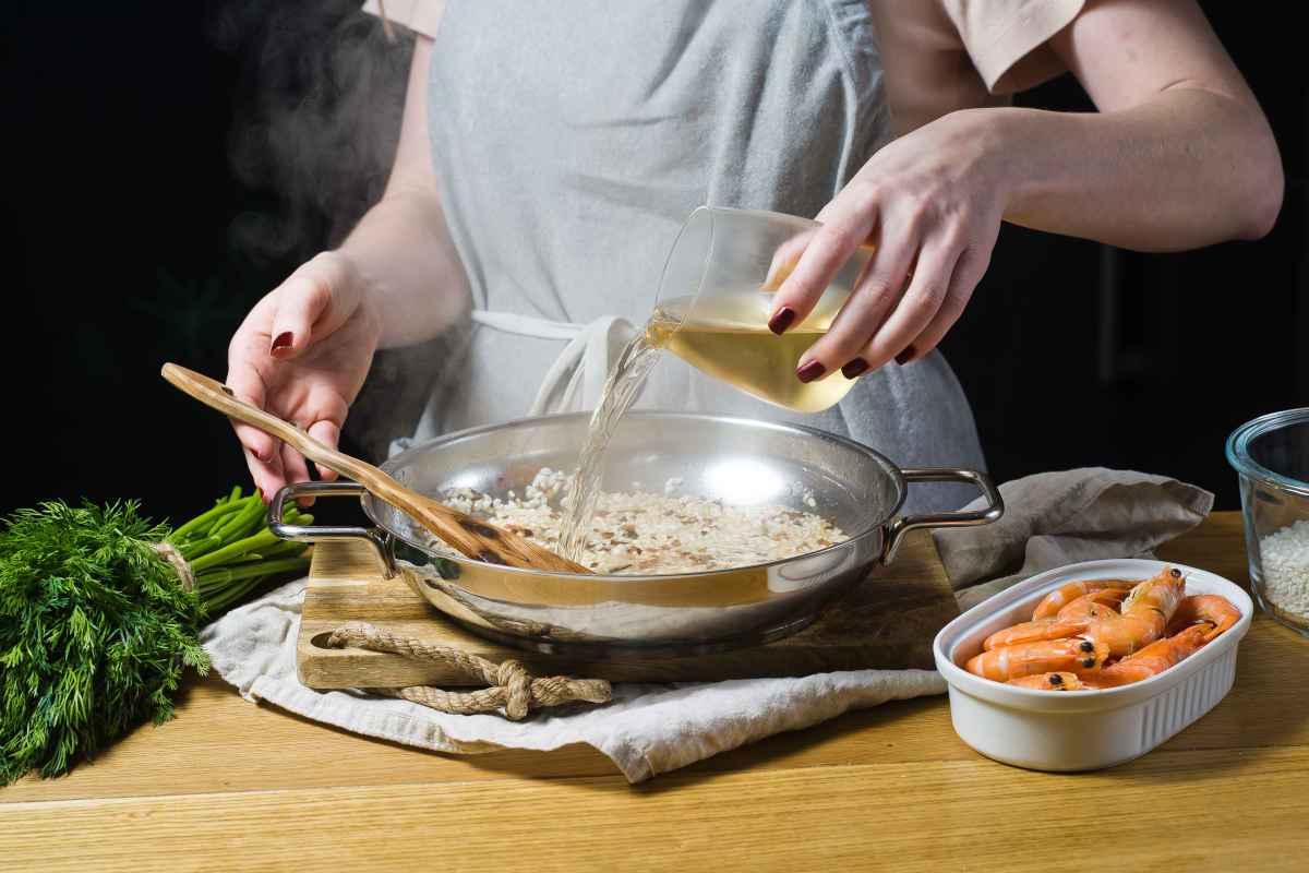 cuoca che usa il vino per sfumare il risotto