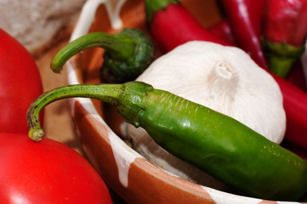 Green and red hot peppers in a bowl