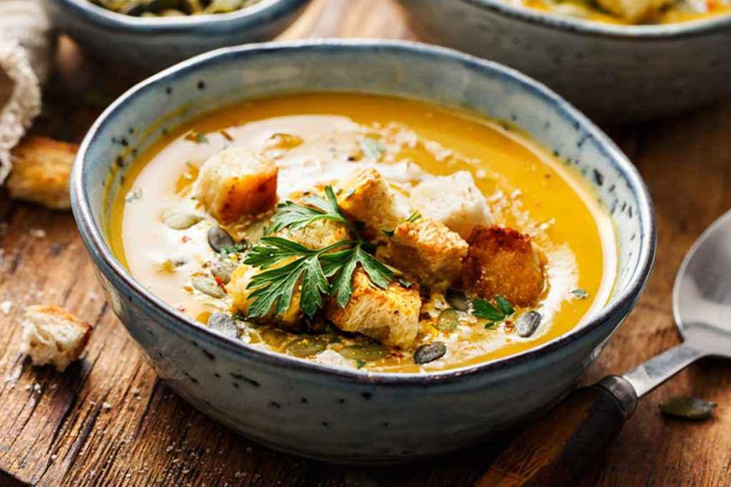 Scodella con zuppa arancione di carote e crostini di pane fritti