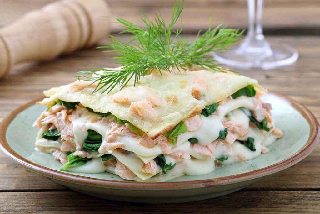 Piatto di lasagna con salmone fresco e verdure