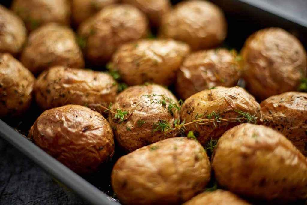 Teglia da forno piena di patate con buccia cotte
