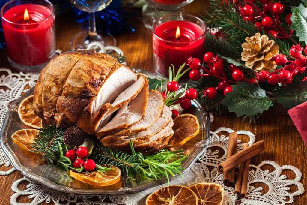 Tavola di Natale con arrosto al centro e decorazioni natalizie
