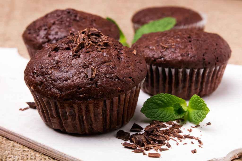 Muffin al cioccolato senza burro decorato con scaglie di cioccolato e foglia di menta