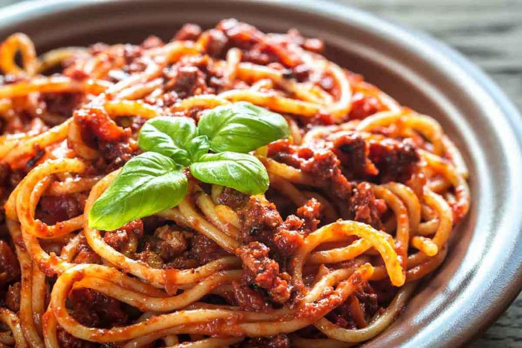 Piatto di spaghetti con ragù di carne alla bolognese e basilico