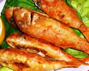 Triglie fritte su letto di lattuga fresca